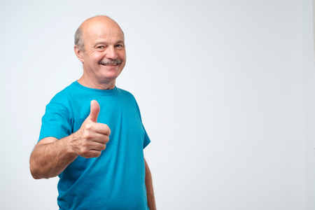 Everything is great. Positive nice mature joyful man in blue t-shirt smiling and showing thumb up sign while looking at you