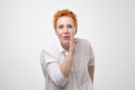 Do not tell anyone concept. Talkative prettyeuropean woman with red hair is saying secret hot braking news isolated on grey background