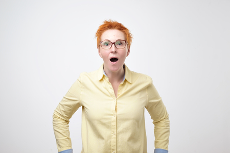 Oh no concept. Headshot of attractive european woman with glasses dressed in yellow shirt looking at camera, keeping mouth wide opened feeling shocked and stressed.