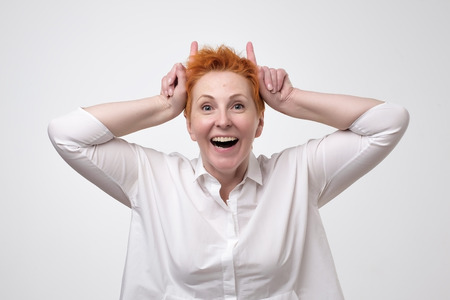Playful pretty mature woman eith red hair shows horns. Tease concept