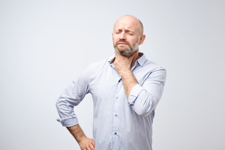Maature european man having oain in throat because of flu. Virus or bacteria infection in winter