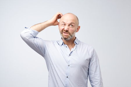 Mature european bearded young male dressed in casual white shirt trying to remember where he put the car keys. I have to remember what my wife told me to do. Negative human emotions and feelings