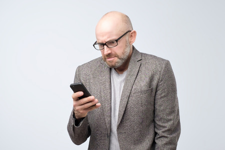 Dissatisfied, grouchy man in casual suit wearing glasses reading articles, doing work searching for information in internet using his phone. Puzzled bald man reading sms with emotional face expression