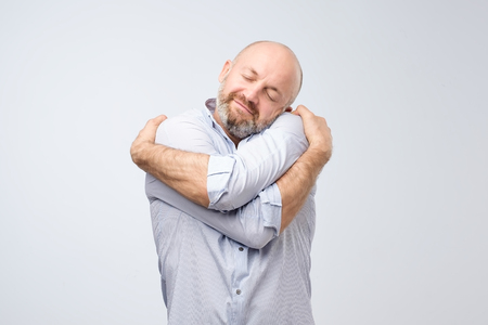 Close-up portret van zelfverzekerde lachende man met knuffelen zichzelf geïsoleerd op een grijze muur achtergrond. Positieve menselijke emotie, gezichtsuitdrukking. Houd van jezelf concept