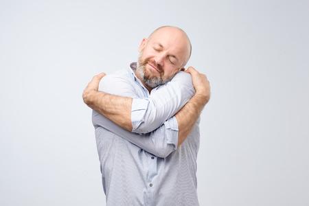 Nahaufnahmeporträt des selbstbewussten lächelnden Mannes, der sich lokalisiert auf grauem Wandhintergrund hält. Positive menschliche Emotionen, Gesichtsausdruck. Liebe dich selbst Konzept