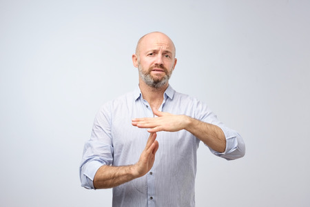 Mature man with beardnshowing time out hand gesture, asking to stop isolated on grey wall background. Too many things to do overwhelmed. Human emotions face expression reaction