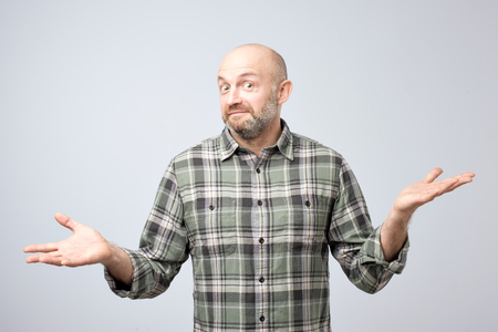 Portrait of confused mature man d standing over white background gesturing with hands. I do not know what to do next. Foto de archivo - 108657697