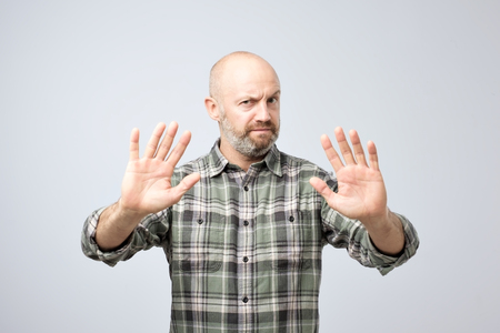 Displeased mature man refusing to accept the idea, stretching hands to camera over grey background. I do not need it concept. Go away from me.