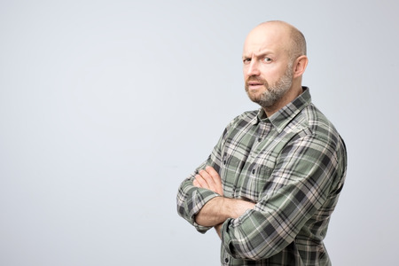 Mature bald man in checkered shirt standing with arms crossed and serious concentrated face at camera, looking suspicious isolated on gray background. May be you are lying to me concept.