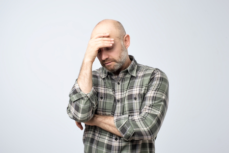 Studio portrait of upset worried sad, depressed, tired man with a headache and very stressed face, isolated on white background, Negative human emotion facial expression