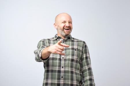 Concepto de broma falsa o mala. Hombre maduro dedo acusador y sonrisa con dientes. Tiro del estudio
