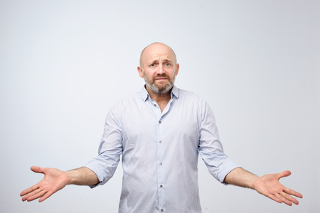 Confused mature bearded man standing and shrugging shoulders isolated over white background. I do not know the solution of this problem concept Foto de archivo - 108829728