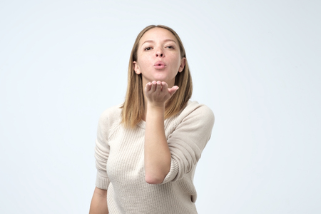 Portrait of young beautiful woman sending an air kiss. Studio shoot
