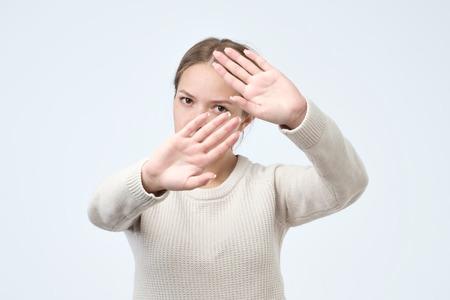 Donna graziosa seria che fa gesto di palma del segno della mano di arresto, isolato sopra fondo bianco. Stai lontano e non toccarmi concetto