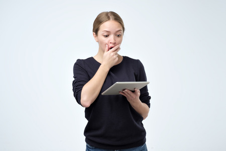 Shocked woman looking at digital tablet with surprise and shock over gray background. Astonishment or hot news in internet Stockfoto - 112815538