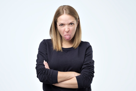 Dissatisfied female model frowns face, has disgusting expression, shows tongue, expresses disgust, irritated with somebody, rejects do something. 免版税图像