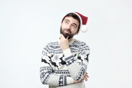 Hispanic man in red christmas cap thinking deeply about gifts, looking up, isolated on grey wall background. Planning new year party. Standard-Bild