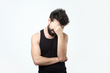 Young guy with a beard covers face with his hand and looks down. He does not want to show his emotions and feelings.