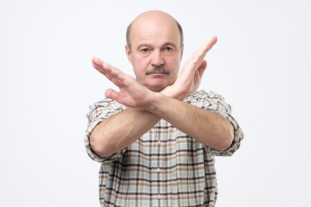 Senior bald man with mustache making stop sign with hand. I do not give you a permission. Guard personal boundaries