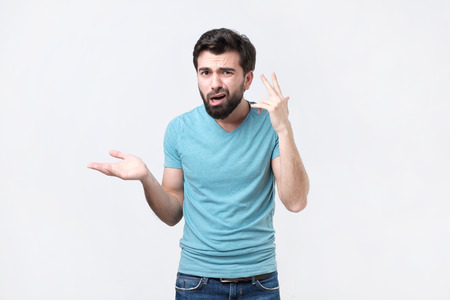 Angry mad young hispanic man gesturing with his finger against temple asking are you crazy. Negative emotion of body language Stock Photo