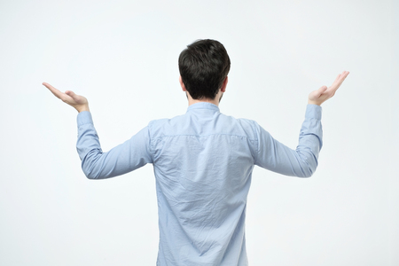 Studio shoot of young man in blue shirt standing back to the camera. He is trying to select something and make a right decision.