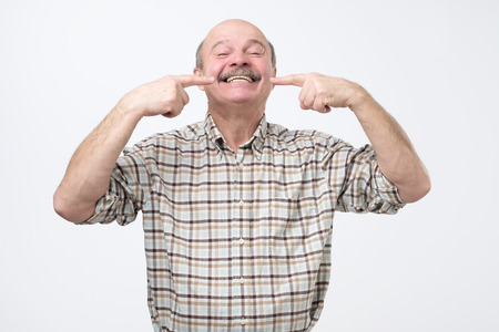 Portrait of happy senior smiling man, pointing on his teeth with fingers. Concept of good teeth care at old age. 免版税图像
