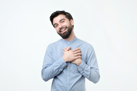 Cheerful hispanic man smiles happily, keeps hands on chest, expresses his positive emotions. Pleased male glad to recieve compliment from woman. 스톡 콘텐츠