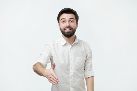Hispanic man with black beard in white shirt welcome his friend or coworker. Studio shoot