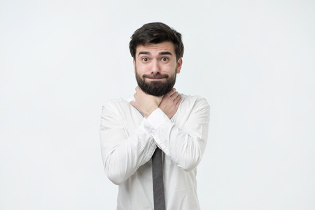 Spanish man with beard and white shirt holding hands by the throat on a gray background, suffocation, choking