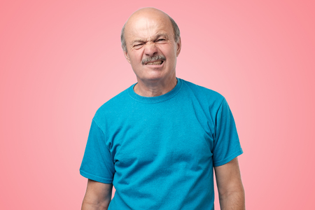 Not sure. Mature adult in blue t-shirt having a doubt with disgust on face standing on pink background. I am confused and do not know the right way concept Foto de archivo - 114209527