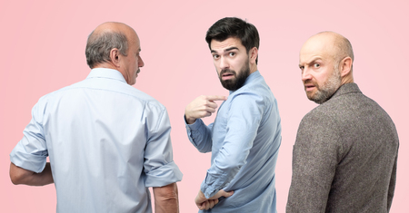 Are you talking about me concept. Horizontal portrait of three man, having doubtful confused uncertain facial expression