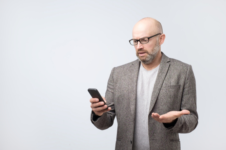 Dissatisfied, grouchy man in suit wearing glasses reading sms, doing work searching for information in internet using his phone. Puzzled bald man reading sms with emotional face expression