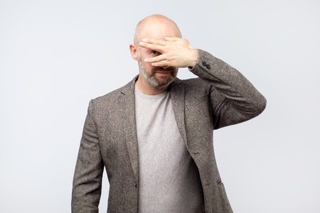 European mature man covering his face by hand and peeping at camera while standing against grey background