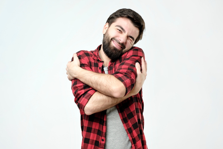 ortrait zelfverzekerde glimlachende man die zichzelf knuffelt. Ik ben het beste concept. Zachte kleding na het wassen