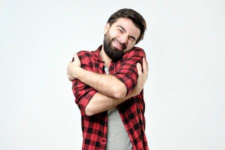 ortrait zuversichtlich lächelnder Mann, der sich selbst umarmt. Ich bin das beste Konzept. Weiche Kleidung nach dem Waschen