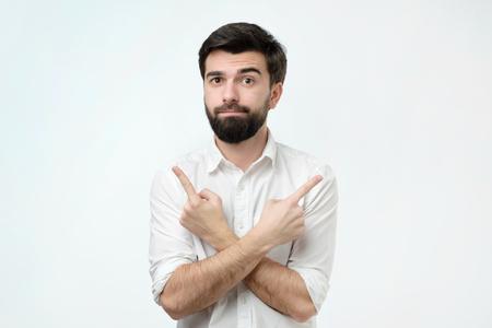 Junger hispanischer Mann, der zwischen zwei Optionskonzepten wählt. Er zeigt mit den Fingern auf verschiedene Seiten. Studioshooting Standard-Bild
