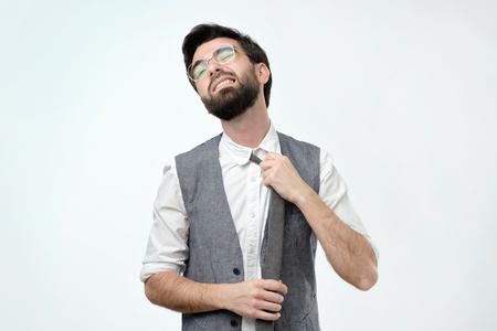junger hispanischer Mann, der Krawatte auf grauem Hintergrund verliert. Er hat das Gefühl, dass er nicht atmen kann. Erstickungsgefahr Standard-Bild