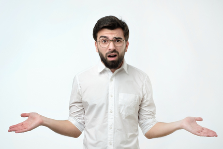Hispanic man in white shirt throws up his hands in disbelief like saying I am not sure now.