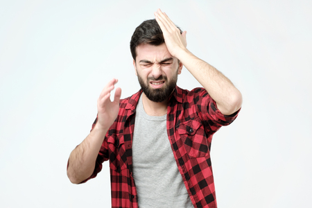 Troubled worried and nervous concerned handsome man pressing hands to head and clenching teeth panicking being in perplexed situation, forgetting important thing Stock Photo