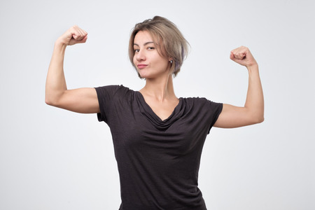 Happy young european woman showing her strong hand. I can do it concept Stock Photo
