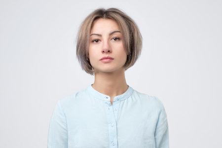 Passport photo. Portrait of european young woman in blue shirt 免版税图像