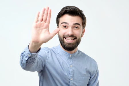 Young man making high five gesture standing isolated on white background. Positive facial emotion Stock Photo