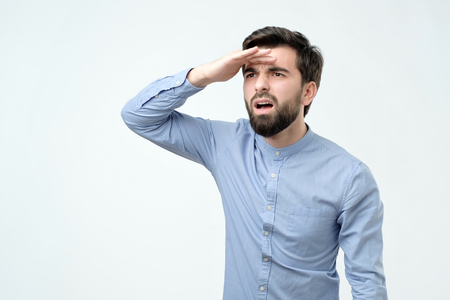 confused young hispanic man with beard looking far away searching for something