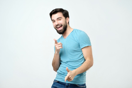 Hey you concept. Portrait of happy hispanic man with beard pointing at you.