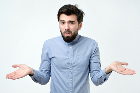 Hispanic man in blue shirt throws up his hands in disbelief like saying I am not sure now.