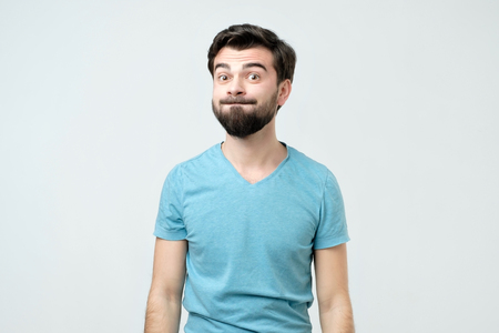 Humorous emotional portrait of grimacing young man. He is blowing his cheeks. He is trying not to laugh