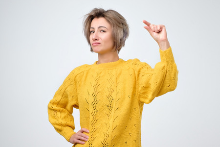 Woman in yellow sweater showing small amount of something with fingers, isolated on white background