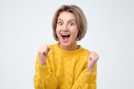 Happy caucasian woman raising fists in winning gesture and celebrating success. Mature woman gaining prize or hitting jackpot. 스톡 콘텐츠