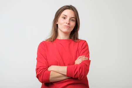 Serious young female wearing red pulover looking at camera, her eyes full of distrust and disappoinment as she has quarrel with boyfriend Stok Fotoğraf