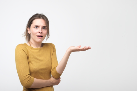 Outraged woman throwing up hand and expressing misunderstanding isolated over blue background